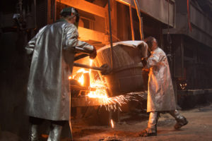 Ladle - Eagle Alloy operators pouring molten steel from a ladle into a mold